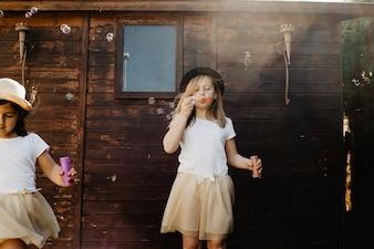 Girls blowing bubbles near wooden building