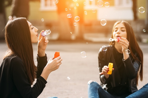 Девушки дует мыльные пузыри