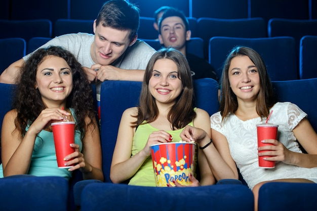 Girls and boys sit in chairs and watch movies.