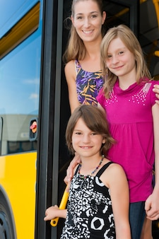 Girls in a bus with their mother