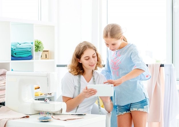 Girls choosing design for sewing
