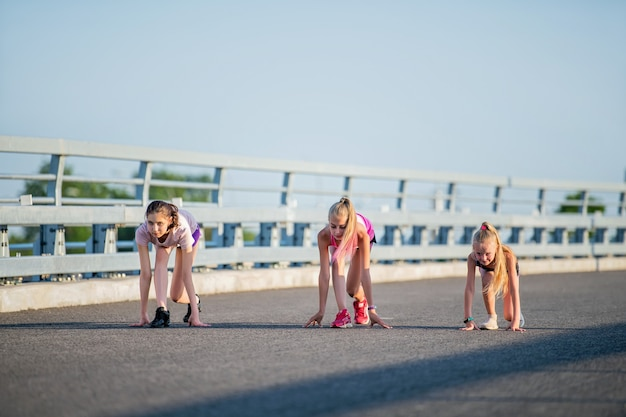 Girls compete on the asphalt road against the evening sky