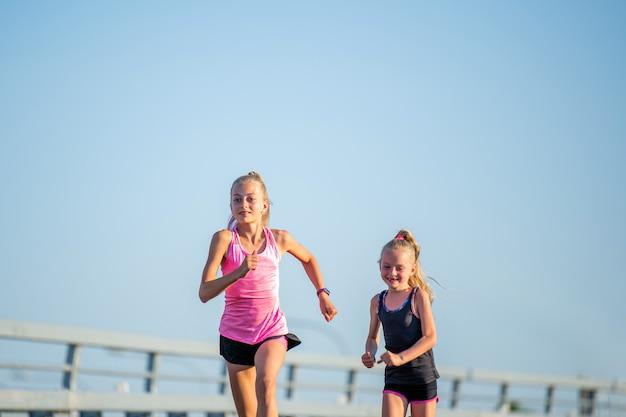 소녀들은 저녁 하늘을 배경으로 아스팔트 도로에서 경쟁합니다.
