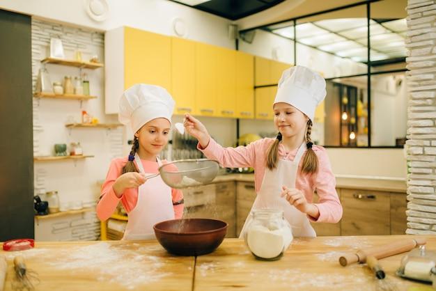 女の子が料理する、キッチンでクッキーの準備