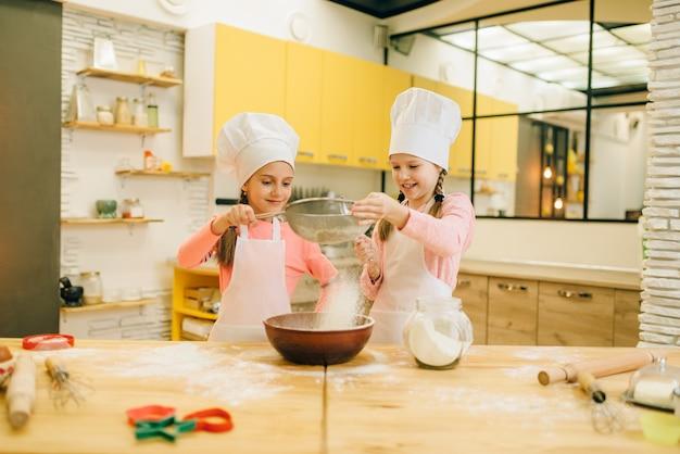 女の子はキャップで料理し、キッチンでクッキーを準備します。ペストリーを調理する子供たち、小さなシェフが生地を作る、子供がケーキを準備する