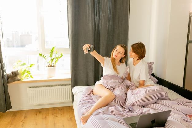 Пара девушек делает селфи в постели, смеясь и веселится в день святого валентина