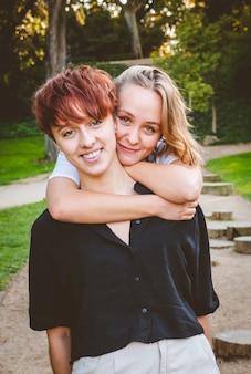 晴れた日に公園で抱き締める恋の女の子のカップル