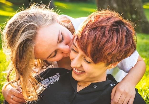 晴れた日に公園の芝生の上に座ってキスを愛する女の子のカップル