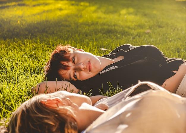晴れた日に公園の芝生の上に横たわっている愛の女の子のカップル