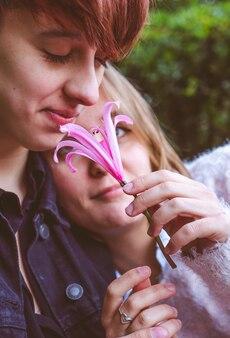 公園でピンクの花で遊ぶのが大好きな女の子のカップル