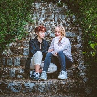 公園の石の階段でリラックスするのが大好きな女の子のカップル