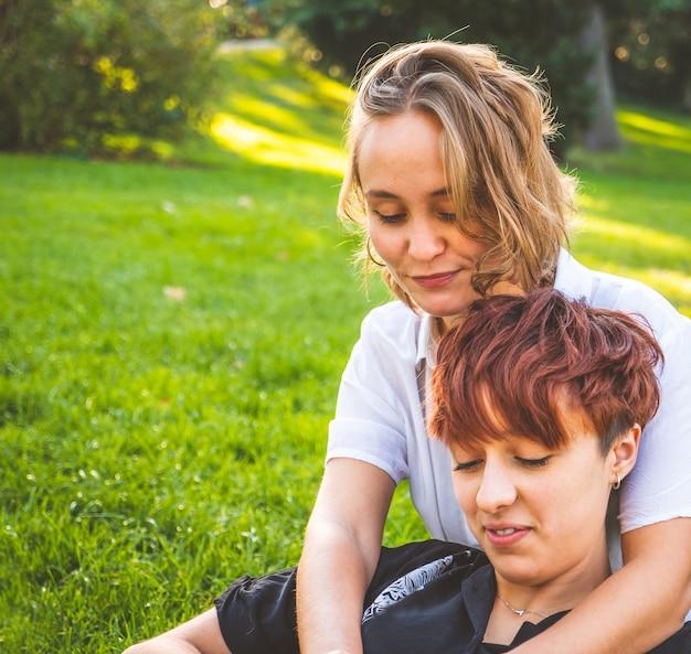 晴れた日に公園の芝生に座って恋をしている女の子のカップル
