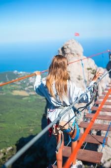 ロープのつり橋の割れ目を横切る女の子