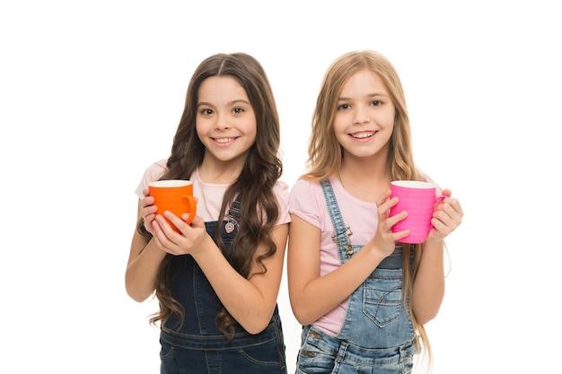 Девочки милые дети с длинными волосами пьют какао или чай. школьницы с кружками во время перерыва на чай. расслабьтесь и зарядитесь энергией. концепция водного баланса. вместе пили чай. сестры или друзья пьют воду. больше энергии.