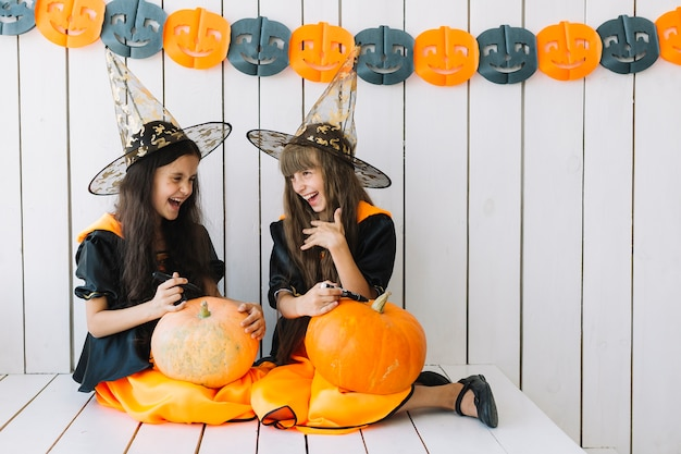 Girls decorating halloween pumpkins and laughing