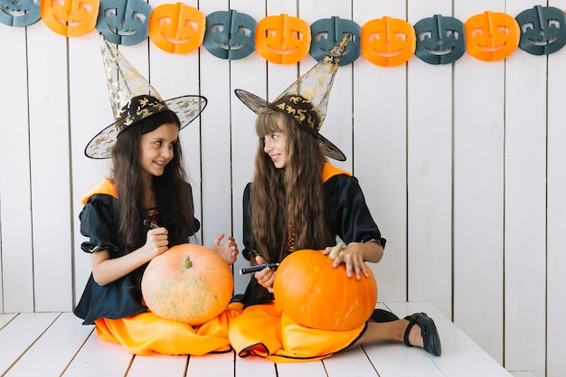 Girls decorating halloween pumpkins
