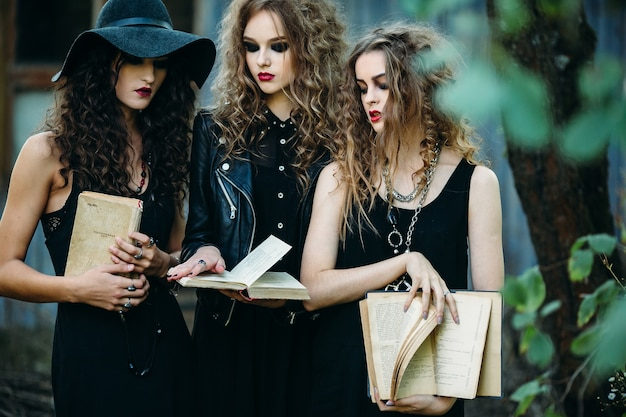 Girls disguised as witches holding open old books in hands