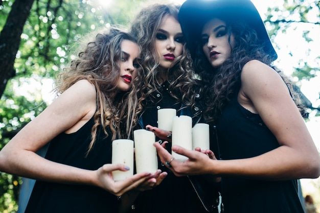 Girls disguised as witches holding white candles
