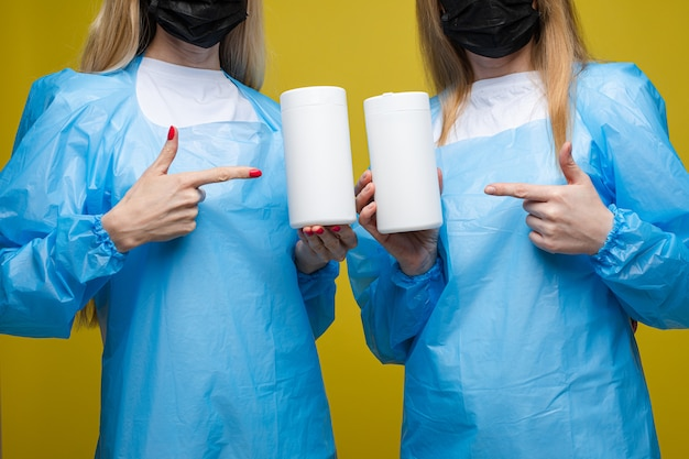 Girls in disposable medical gowns and masks on their faces holding antibacterial wipes