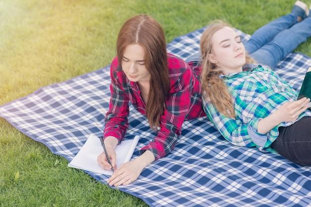 Girls doing homework on picnic cloth