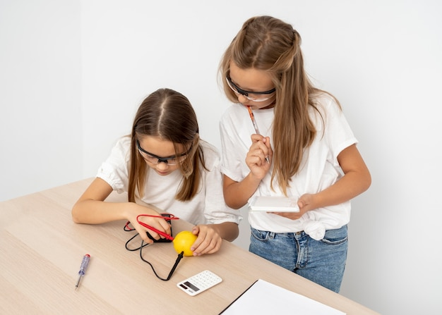 Девочки проводят научные эксперименты с лимоном и электричеством