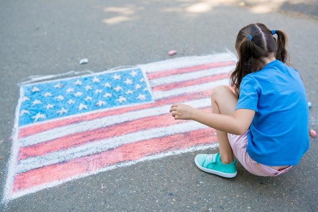Девушки рисуют американский флаг цветными мелками на тротуаре