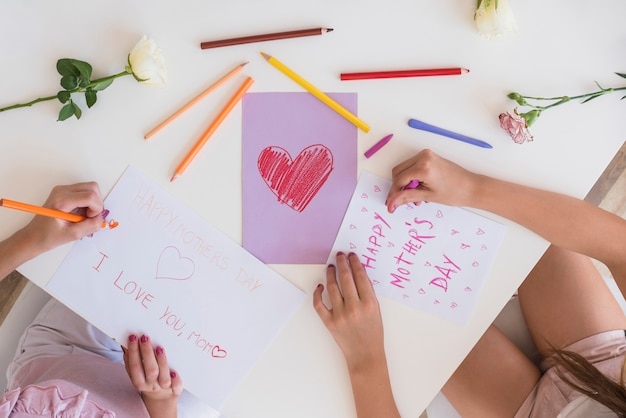 Girls drawing greeting cards for mothers day