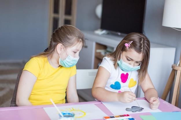 自宅で一緒に無菌マスクで隔離されている女の子。子供の頃のゲーム、芸術の描画、在宅滞在のコンセプト