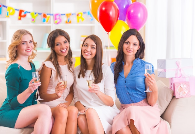 Girls drinking champagne and smile at home party.