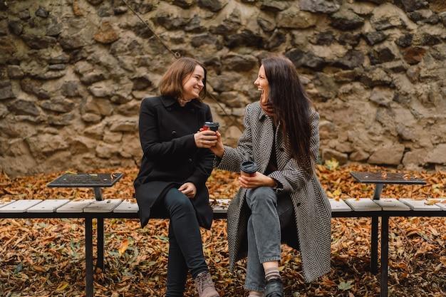 Девушки пьют кофе в парке. друзья и образ жизни