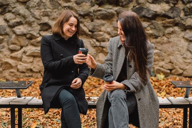 公園でコーヒーを飲む女の子。友達とライフスタイル