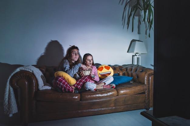 Girls enjoying movie in dark room