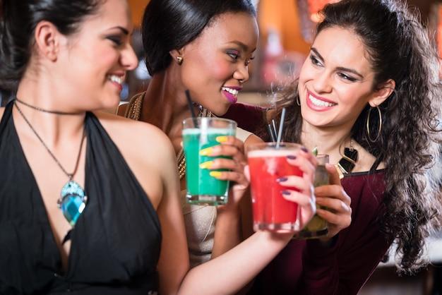 Девушки наслаждаются ночной жизнью в клубе, пьют коктейли