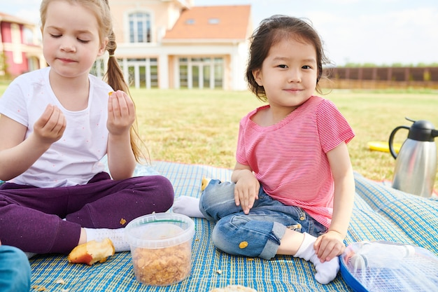 Girls enjoying picnic on lawn