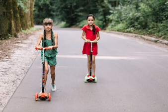 Girls enjoying riding scooter on road