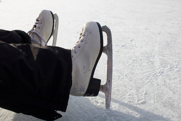 Girls feet with ice skates, close up and place for text