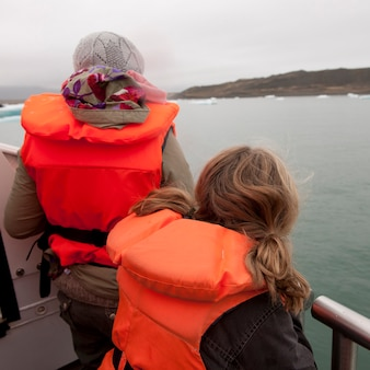 Girls in fluorescent orange life preservers on boat on glacial lake