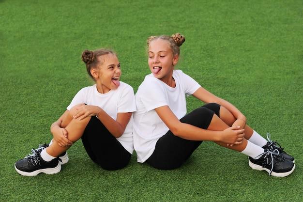 女の子は馬鹿になって遊び場で楽しんでいます。スポーツウェアを着た女の子姉妹がスタジアムの緑の芝生に座り、お互いに舌を出し合う。白いtシャツ。私たちの生活の中でのスポーツ。
