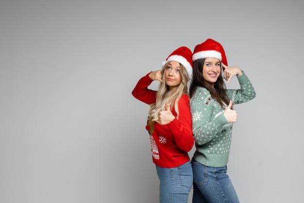 빨간색과 흰색 크리스마스 모자를 쓴 여자 친구가 무언가를 추천합니다.