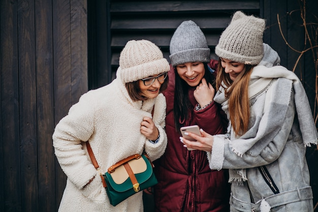 Girls friends meeting together at winter time outside the street