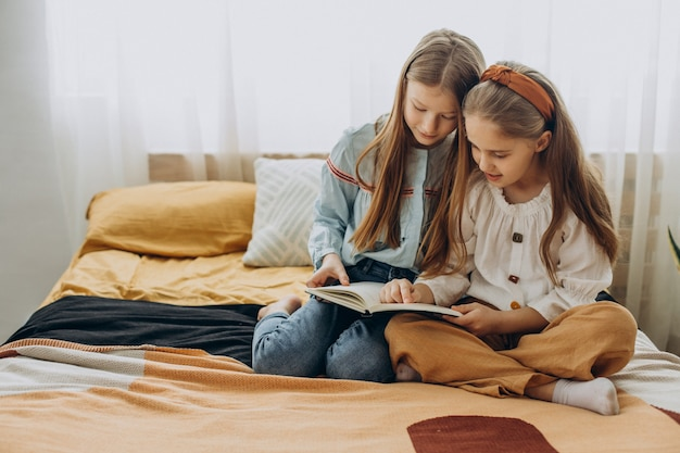 Girls friends reading book together at home
