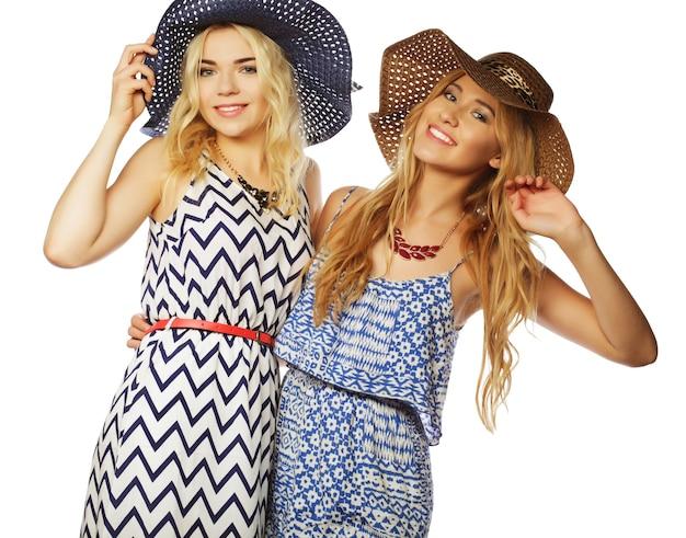 여름 드레스와 밀짚 모자를 쓰고 웃고 포옹하는 여자 친구