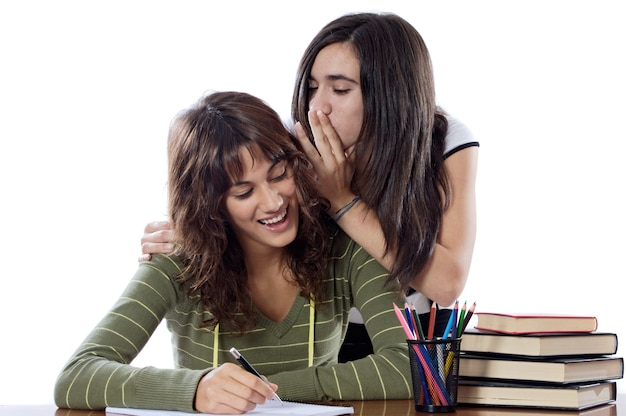 Girls friends whispering while studying