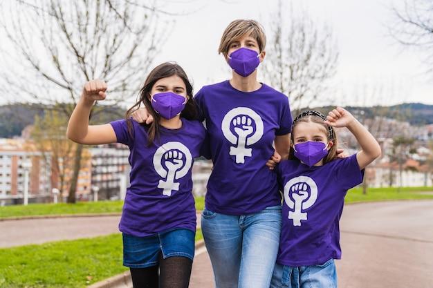 3月8日の国際女性デーの女性の権利を主張する働く女性のシンボルが付いた紫色のtシャツを着て、コロナウイルスのフェイスマスクを着ている家族の女の子