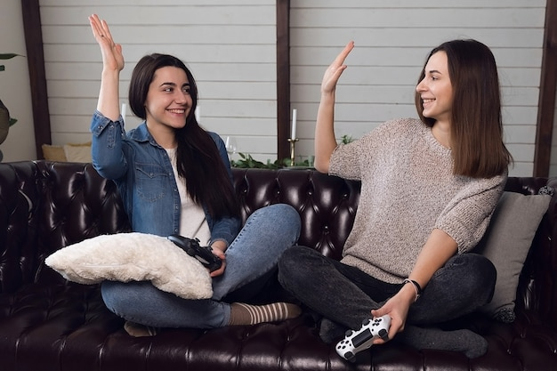 소녀들은 서로에게 5 개를주고 여성 게이머들은 게임 콘솔을 플레이하며 집에서 즐겁게 지냅니다. 고품질 사진