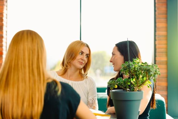 여자 험담. 카페에서 말하는 세 명의 가장 친한 친구. 커피 숍의 테이블에 앉아있는 동안 여성 친구가 가짜로 웃고 웃고. 사회와 우정 개념.