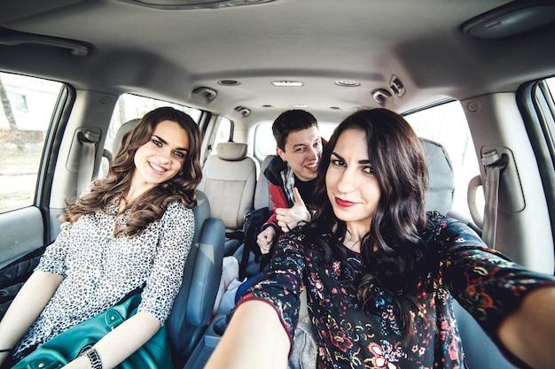 Girls and guy taking selfie in car