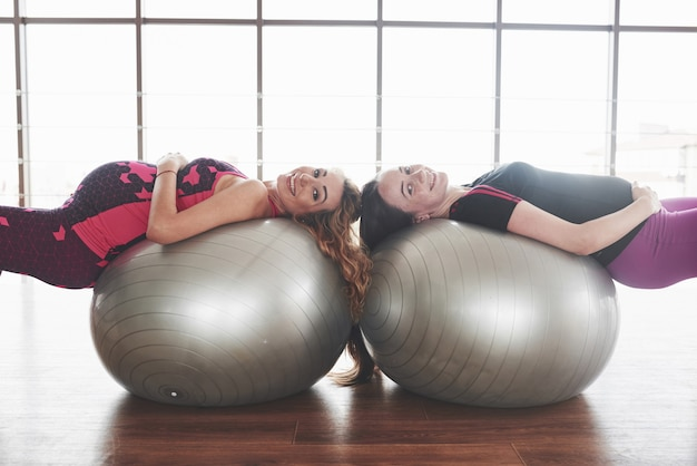 Girls in the gym laying on two stability balls while pregnant and smiling.