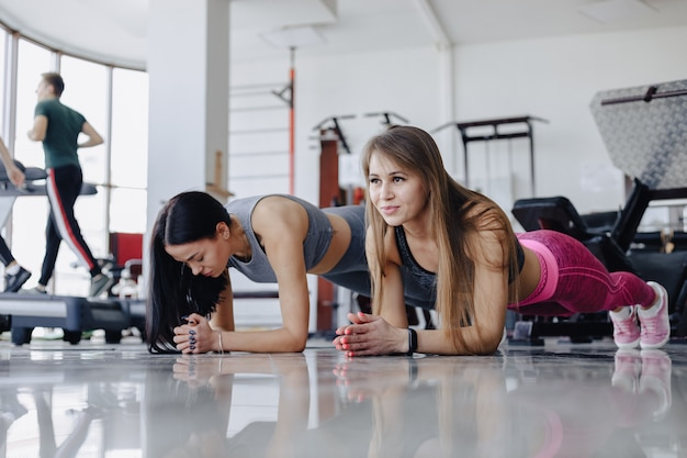 Girls in the gym stand in plank