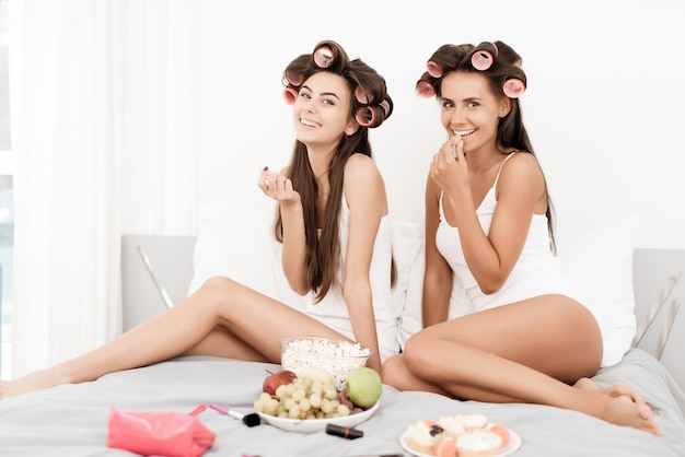 Girls in hair curlers are sitting on the bed.